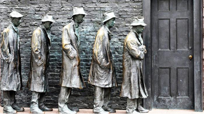 statue di poveri in fila