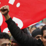 Manifestazione di migranti con i pugni alzati